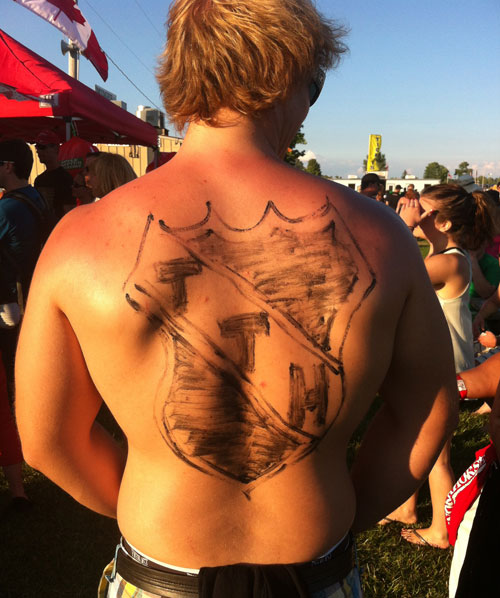 A young man with a Tragically Hip logo covering his bare back